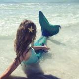 meisje aan strand met zeemeerminstaart